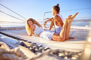 Portrait smiling woman relaxing on sunny catamaranの写真素材 [FYI02185510]