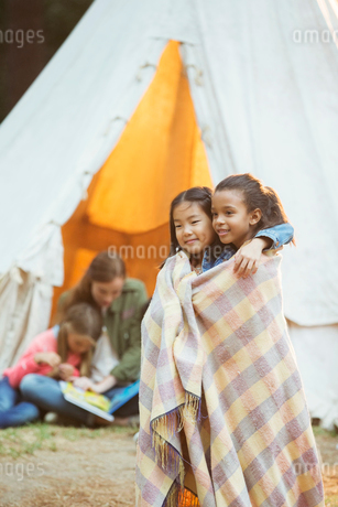 Girls wrapped in blanket at campsiteの写真素材 [FYI02185527]