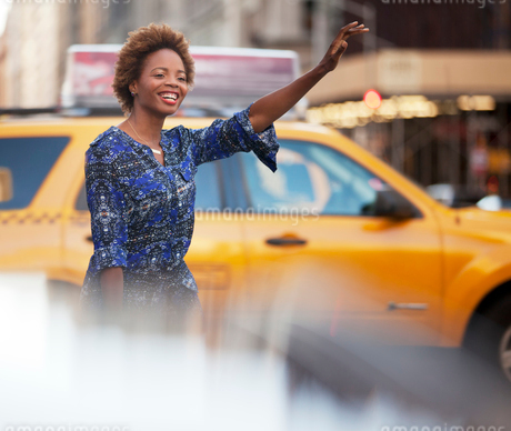Woman hailing taxi on city streetの写真素材 [FYI02185537]