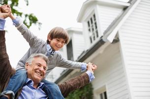 Man carrying grandson on shoulders outdoorsの写真素材 [FYI02185546]