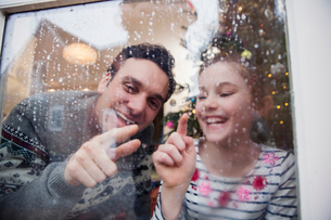 Father and daughter drawing in condensation on wet winter windowの写真素材 [FYI02185554]