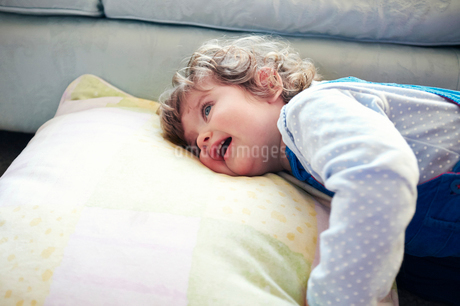 Girl laying on pillow in living roomの写真素材 [FYI02185555]