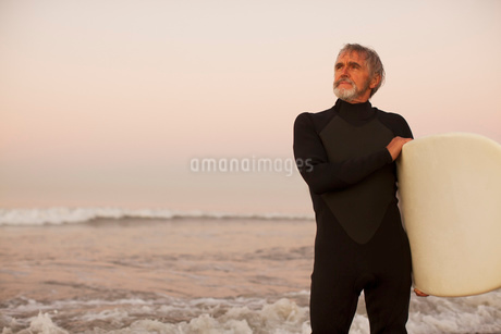 Older surfer carrying board on beachの写真素材 [FYI02185558]