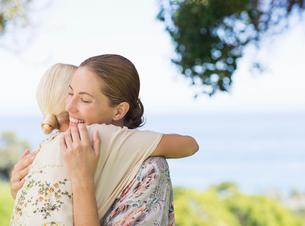 Women hugging outdoorsの写真素材 [FYI02185570]