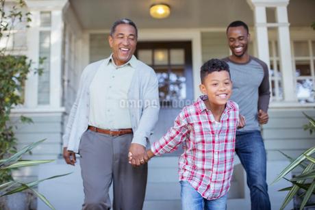 Multi-generation men holding hands outside houseの写真素材 [FYI02185625]