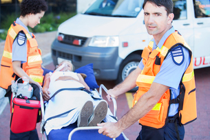 Paramedics wheeling patient on stretcher in hospital parking lotの写真素材 [FYI02185628]