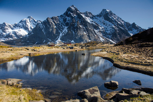 Snow on remote, sunny, craggy mountains above water, Maervoll, Lofoten, Norwayの写真素材 [FYI02185632]