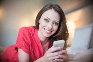 Portrait of smiling woman wearing red dress lying on bed with smartphoneの写真素材 [FYI02185672]