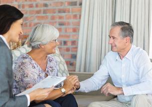 Financial advisor talking to couple on sofaの写真素材 [FYI02185674]