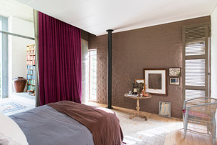 Bed, side table and pictures in rustic bedroomの写真素材 [FYI02185714]