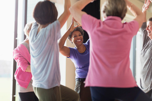 Smiling active senior woman exercising, practicing yoga tree poseの写真素材 [FYI02185730]