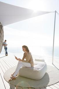 Woman using digital tablet on modern balconyの写真素材 [FYI02185737]