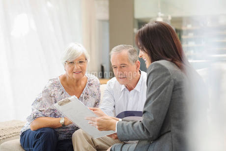 Financial advisor talking to couple on sofaの写真素材 [FYI02185785]