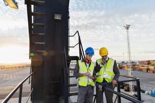 Workers using walkie-talkie on cargo craneの写真素材 [FYI02185821]