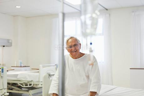 Older patient sitting on bed in hospital roomの写真素材 [FYI02185830]