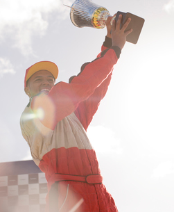 Racer holding trophy at award ceremonyの写真素材 [FYI02185864]