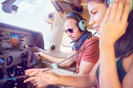 Pilot and copilot flying airplane, checking navigational equipmentの写真素材 [FYI02185873]