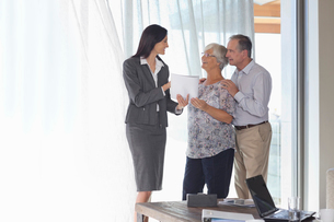 Financial advisor talking to couple in officeの写真素材 [FYI02185887]