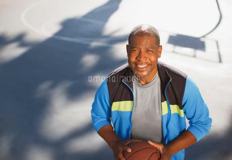 Older man playing basketball on courtの写真素材 [FYI02185891]