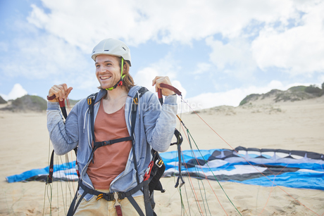Smiling, confident paraglider with parachute on beachの写真素材 [FYI02185899]