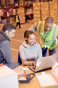 Workers using laptop in warehouseの写真素材 [FYI02185910]