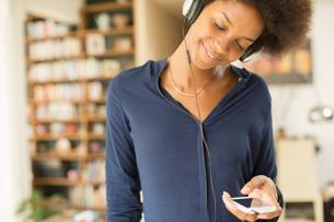 Woman listening to headphones in living roomの写真素材 [FYI02185918]