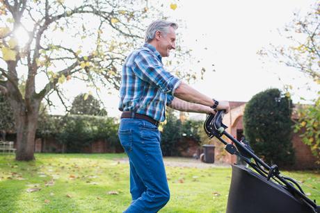 Senior man moving lawn with lawnmower in autumn backyardの写真素材 [FYI02185955]