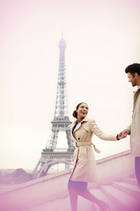Couple descending stairs by Eiffel Tower, Paris, Franceの写真素材 [FYI02185962]