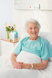 Portrait of smiling aging patient in hospital bedの写真素材 [FYI02185968]