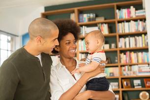 Couple holding baby in living roomの写真素材 [FYI02186013]