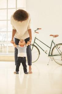 Mother helping baby boy walk in living roomの写真素材 [FYI02186017]