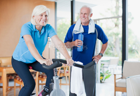 Older woman riding exercise bike at homeの写真素材 [FYI02186023]