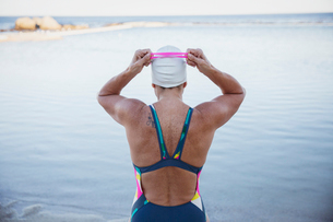Female open water swimmer adjusting swimming goggles at oceanの写真素材 [FYI02186103]