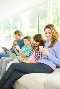 Family using technology on sofaの写真素材 [FYI02186114]