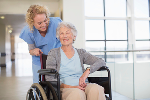 Nurse and aging patient smiling in hospital corridorの写真素材 [FYI02186118]