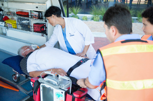 Doctor examining patient on ambulance stretcherの写真素材 [FYI02186129]