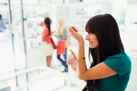 Woman trying out perfume in drugstoreの写真素材 [FYI02186165]
