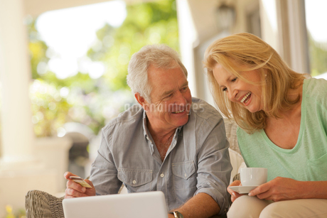 Smiling couple drinking coffee and shopping online on patioの写真素材 [FYI02186166]
