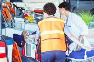 Paramedics wheeling patient out of ambulanceの写真素材 [FYI02186196]