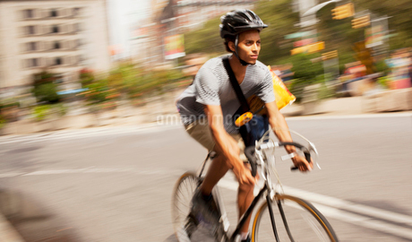 Man riding bicycle on city streetの写真素材 [FYI02186223]