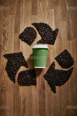 Coffee beans forming recycle symbol around green recyclable coffee cupの写真素材 [FYI02186231]