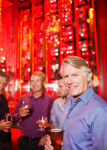 Portrait of smiling mature man holding beer glass in nightclub, friends in backgroundの写真素材 [FYI02186242]
