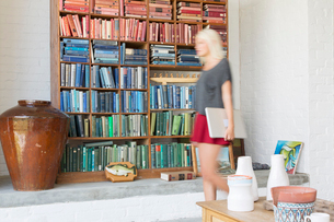 Blurred view of woman walking by book shelvesの写真素材 [FYI02186339]