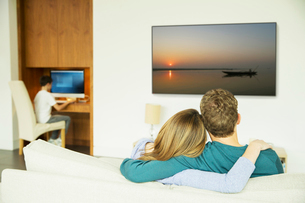 Couple watching television in living roomの写真素材 [FYI02186346]