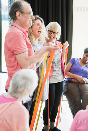 Smiling active seniors and instructor stretching, exercising with strapsの写真素材 [FYI02186360]
