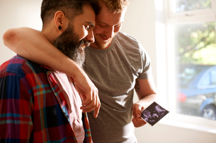 Affectionate male gay couple looking at ultrasound photoの写真素材 [FYI02186362]