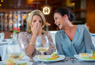 Two mature women laughing in restaurantの写真素材 [FYI02186416]