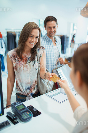 Woman paying with credit card in clothing storeの写真素材 [FYI02186423]