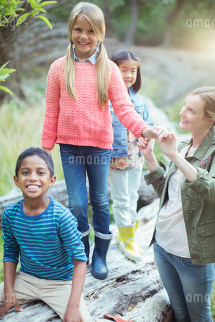 Students and teacher climbing on logの写真素材 [FYI02186438]