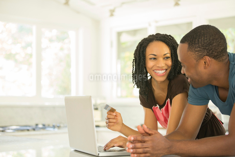 Happy couple shopping online at laptop in kitchenの写真素材 [FYI02186471]